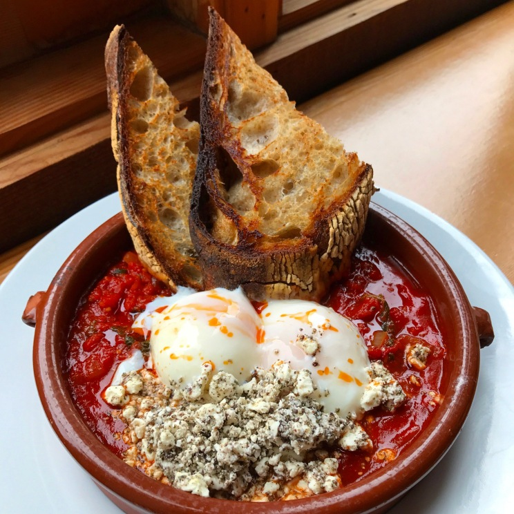 Shakshouka two slow-poached eggs in a spiced tomato sauce with kale, feta, zatar and toast